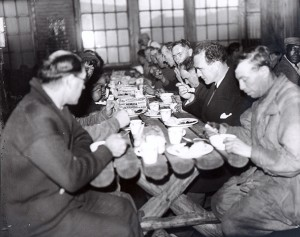 Detroit Mayor Frank Murphy (black suit, white handkerchief) eats with men in the Fisher Lodge on Christmas Eve, 1932.