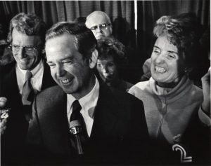 Governor Milliken at a microphone with people crowded around him, 1978. HS9505