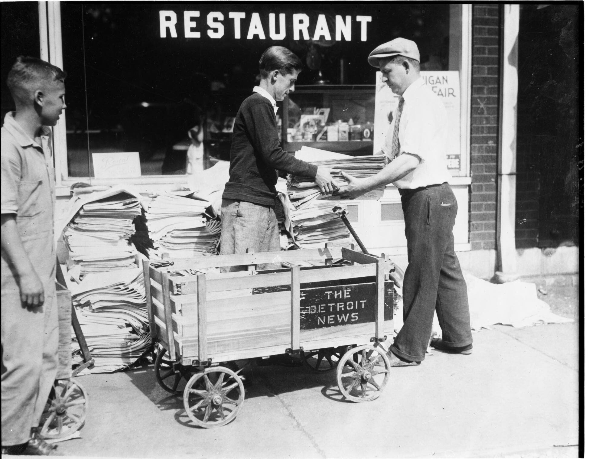 Newspaper carriers with wagon of Detroit News issues.