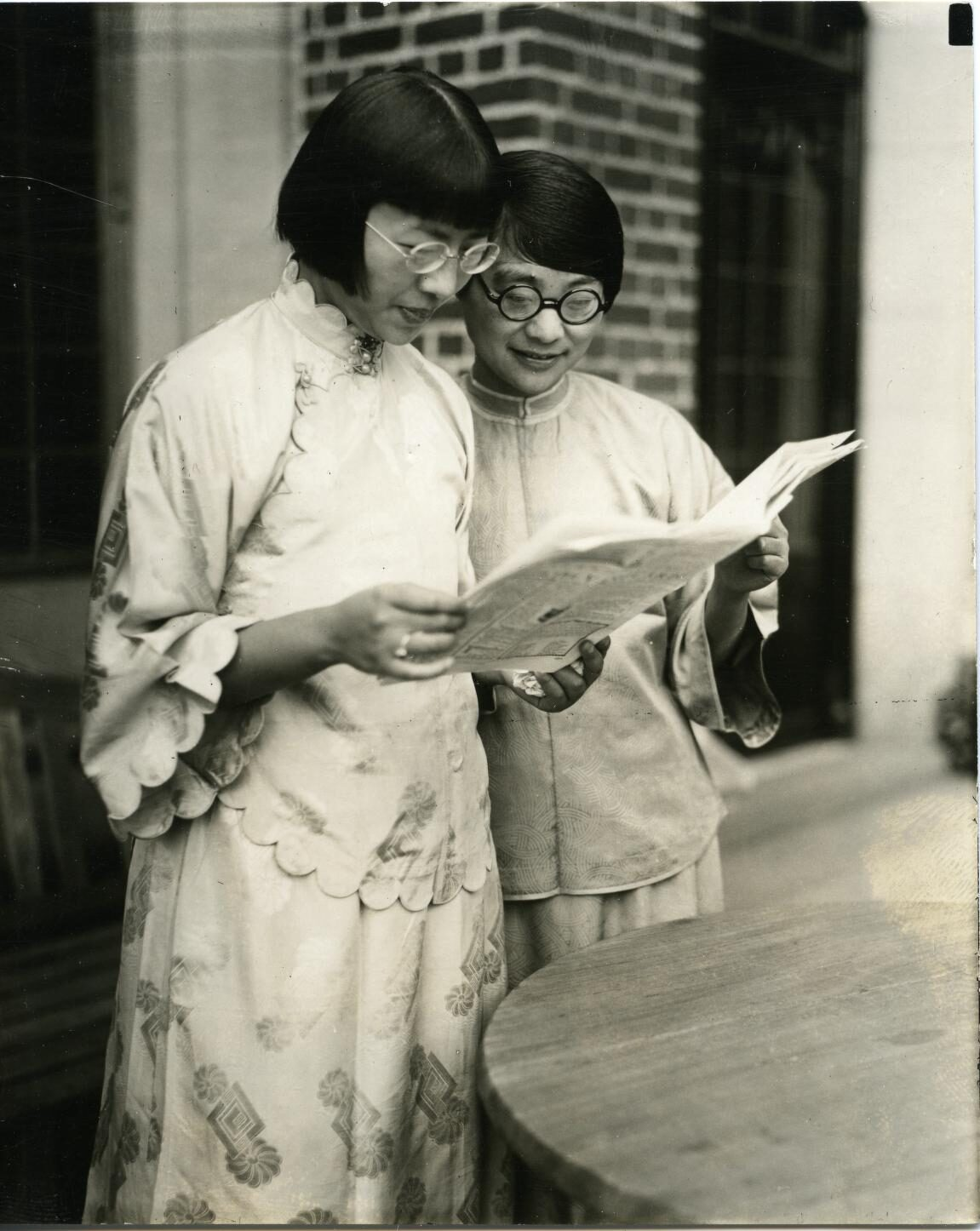 Students Shui Ching & Ao Dju reading a book on patio.